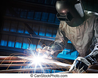 welder - man welding in workshop with safety precaution