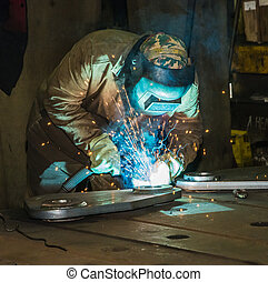 Welder at work in the blinding light of bright splashes of red-hot metal.