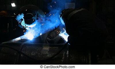 Welder welding metalwork in a factory