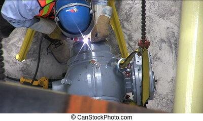 welder welding pipe from above
