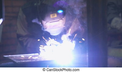 Welder welding the electrode parts - Close-up of male welder...