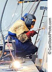 welder with protective mask welding metal