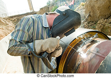 welder worker - welder works with electrode in protective...