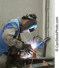 Welder working, welding steel tubes at a furniture factory