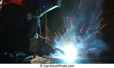 Welder works in a protective mask in shop at the factory. ...