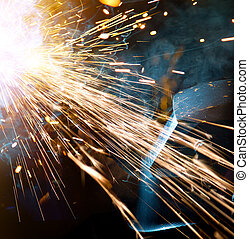 Welders in action with bright sparks. Construction and ...