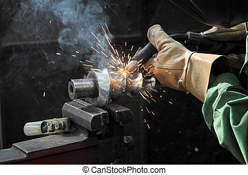 Welding - Closeup photo of arc welding of a steel shaft with...