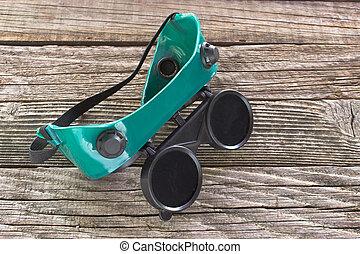 Welding glasses on wooden background