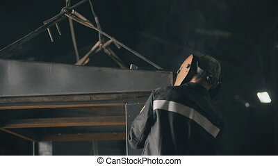 Welding in metal industry. A factory worker welding with...