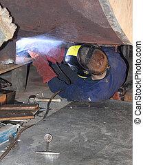 Welding - A welder welding a new support in position on an...
