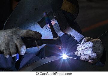 welding metal part in factory.