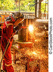 Welding Piping - Worker with protective mask sparks piping...