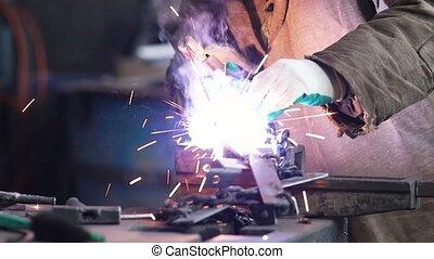 Welding process. A man worker doing his job in the dark. ...