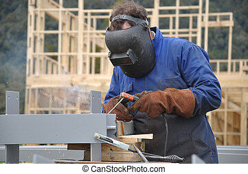 A welder prepares steel beams for a building at a construction site
