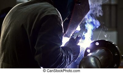 Welder at work in factory, industrial details