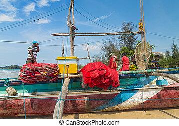 Fisherman preparing fishing net on a boat