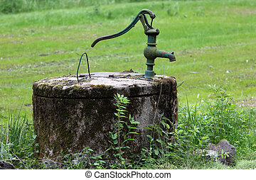 An old-fashioned drilled well with a manual pump.