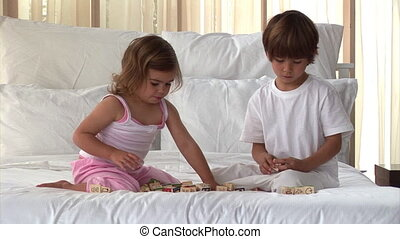 Well-behaved children playing on the bed at home