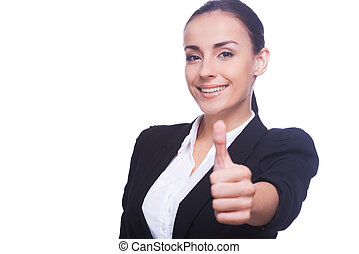Well done! Beautiful young woman in formalwear showing her thumb up and smiling while standing isolated on white