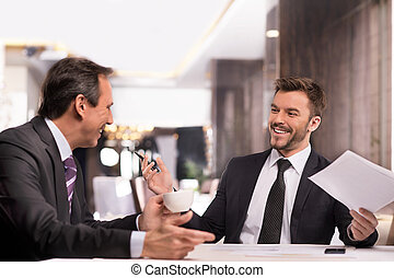 Well done! Two cheerful business people in formalwear discussing something and smiling while sitting at the restaurant