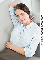 Well dressed beautiful woman resting on sofa