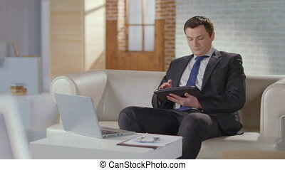 Well-dressed businessman searching scrolling on tablet in...