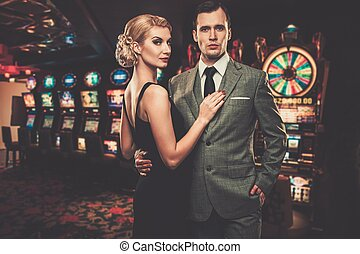 Well-dressed couple against slot machines