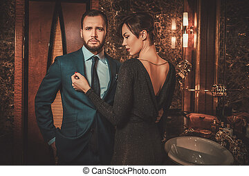 Well-dressed couple in luxury bathroom interior.