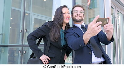Well dressed man and woman take selfie with smart phone outside business complex