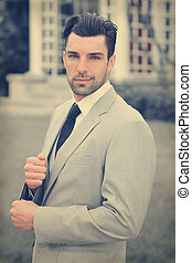 Handsome young businessman outdoors in stylish suit with overall subtle retro toning and feel
