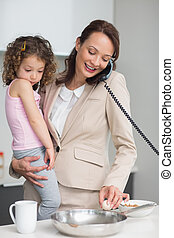 Well dressed mother with daughter preparing food while on call