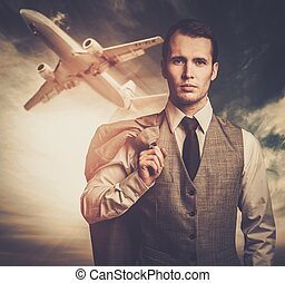 Well-dressed traveling businessman against plane in the sky