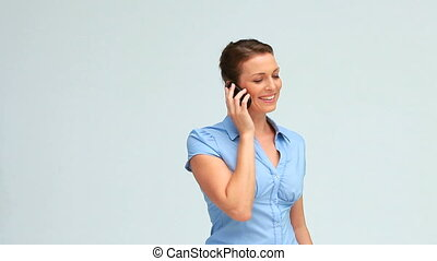 Well-dressed woman calling with a mobile phone against white...