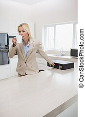 Well dressed woman drinking coffee while holding briefcase in the kitchen at home