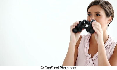 Well-dressed woman looking through binoculars against white...