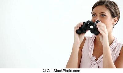 Well-dressed woman looking through binoculars