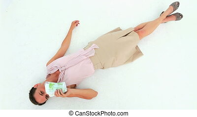 Well-dressed woman lying on the floor throwing banknotes...