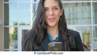 Well dressed woman on her smart phone looks up and smiles at the camera