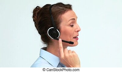 Well-dressed woman speaking with a headset against white...