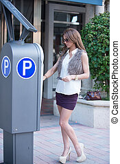 Well dressed women at a parking meter