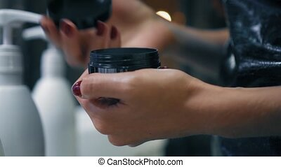 Well-groomed female hands open a beauty product. Woman open black jar of cream. Closeup