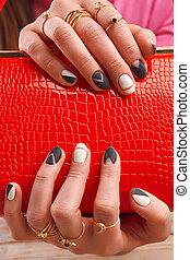 Well-groomed hands holding red handbag. Red lacqured clutch...