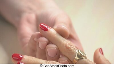 Well-groomed hands receiving manicure close up.