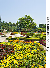 Well-groomed park with a fountain, colors, bushes and trees.