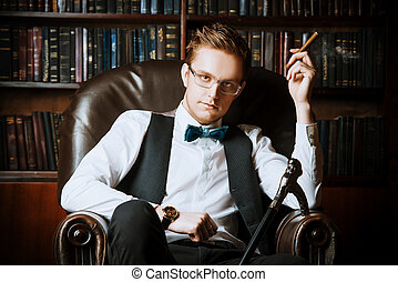well-groomed - Elegant young man in a suit sitting in...