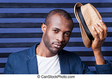 Well hello! Handsome young African man holding his hat and looking at camera while standing against striped background
