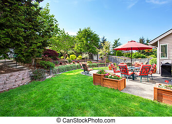 Well kept garden at backyard with concrete floor patio area and opened red umbrella. Northwest, USA