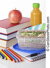 Well prepared school lunch with books and pencils on white...