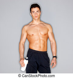 Well Shaped - Muscular and tanned male isolated on grey