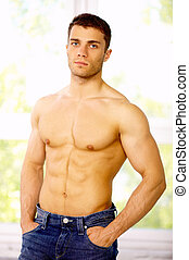 Well Shaped - Muscular and tanned male standing near the...
